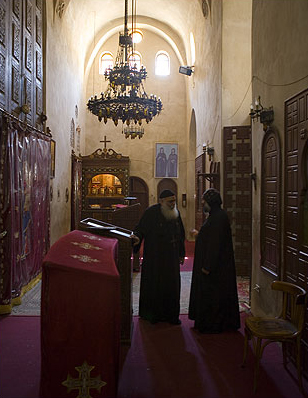 Two elder monks silently  talk in one of the back chambers in the Monastery of the Romans