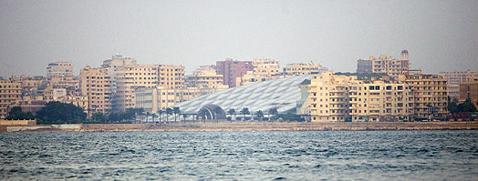 A far shot from the bay of the Library of Alexandria peeking out from other buildings