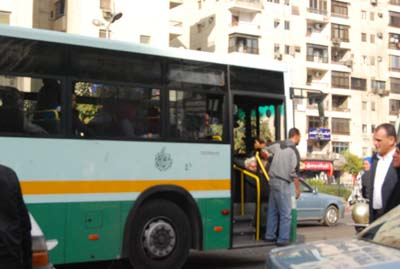 Picture of Public transportation bus painted pale green, dark green and an orange stripe