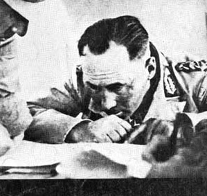 An obviously intense Rommel studies the battlefield maps at al-Alamein
