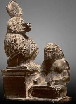 Statue of a scribe writing at the feet of Thoth as a lunar baboon