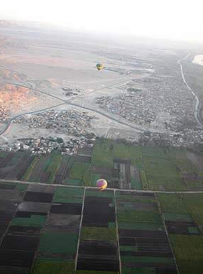 Several Balloons float along below us as we fly above the West Bank of Luxor, Egypt