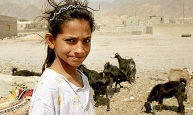 A young Bedouin girl taking care of the family's goats