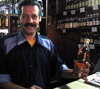 A vendor at Simon holds a bottle of Johnny Walker