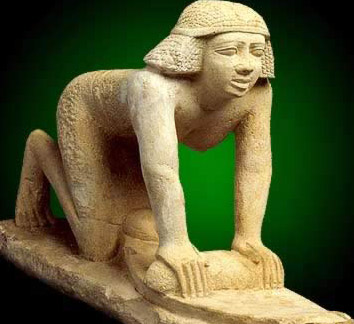 Statuette of a kneeling   woman grinding grain on a quern to make flour dating to the 5th Dynasty