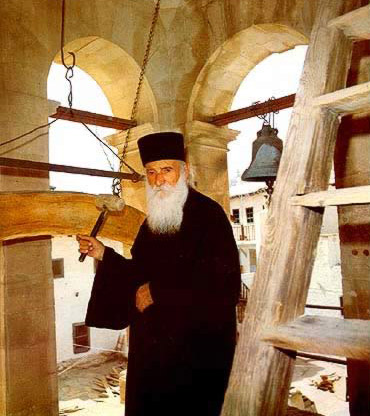 A monk striking the wooden semantron (talanton) with one of the bells in the background