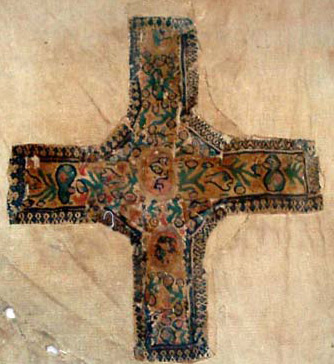 A fragment of tapestry woven from woolen thread. The cross is adorned with human figures