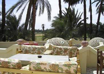 Domes mix among tables on the roof terrace restaurant of the El Nakhil Hotel on the West Bank at Luxor