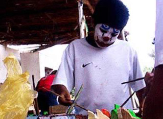 A young boy with a painted face doing some artwork
