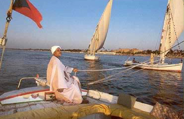 A felucca captain sails his small boat on the Nile River