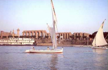 A felucca passes by the Temple of Luxor at Luxor.