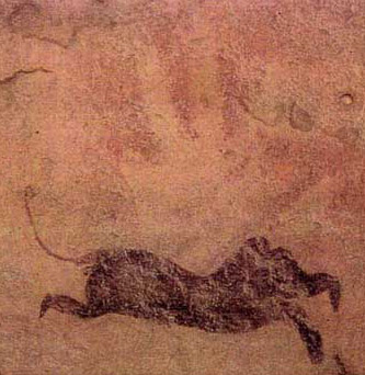 Feline appearing animal partially atop a hand print at Gilf Kebir in Egypt