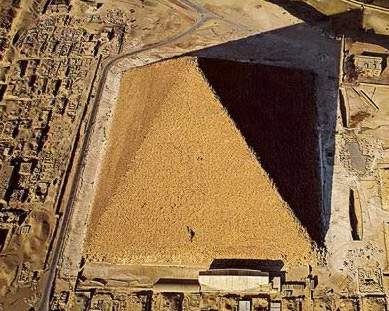 An excellent view of the Great Pyramid of Khufu showing the solar boat memorial in front and other boat pits to the side