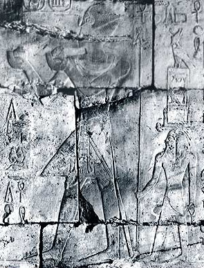 Tuthmosis III making offerings followed by his ka, wearing his Horus name on its head. The ka is also holding in his right hand, a long cane topped by the pharaoh's head