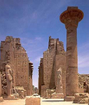 One of the towering columns of the Kiosk of Tahraqa and the second pylon of the Temple of Amun in the brackground, fronted by colossal statuess of Ramesses II