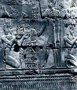The King makes offerings such as bread before Amun (standing)