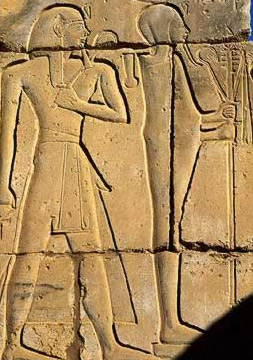 Seti I stands behind Khonsu  in a relief in the Gu8rna Temple of Seti I