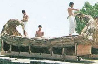 Modern Egyptians, dressed as ancient ones, work on a reed boat at the Pharaonic Village