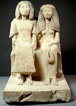 Yuny and his wife, Renenutet, Asyut, early Dynasty 19, late reign of Seti I or early reign of Ramesses II. She holds a menit necklace in her left hand
