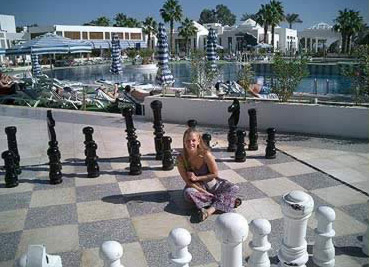 Rachel (Tigger) plays chess piece, while behind her is the main pool, with the main restuarant to the left and the acitivity cetner to the right