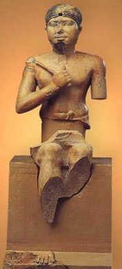 Neferefre sitting on his throne holding a mace against his chest. The statue is made of rose colored limestone