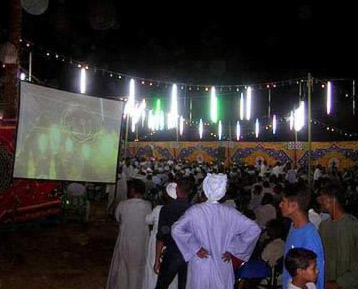 So many attend that some must watch the festivities on video