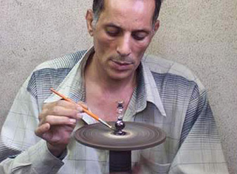 Painting a perfume bottle on a wheel for even distribution