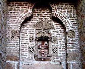 Above the present day  door to the church (eastern apses of the original church. The carvings  in the niche are older.