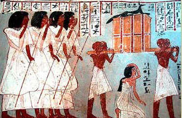A woman kneels below a casket, probably holding the canopic equipment (containing the viscera of the deceased), carried by four servants and surmounted by a figure of Anubis.