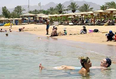 Tourists relax on a slightly less crowded beach the day after the Sharm bombing