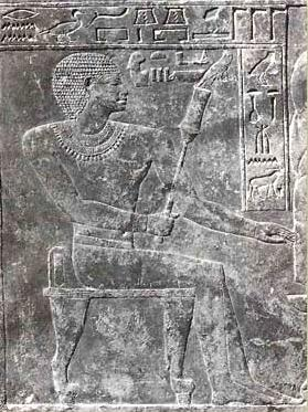 The stele of Sarenenutet, steward of the double granary, showing him seated and holding a sekhem scepter