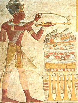 Seti wearing a blue  crown to emphasize his military prowess, burns incense over an offering