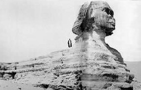 The Sphinx showing the scale of the head against a standing human figure and the characteristic erosion  of the Sphinx body