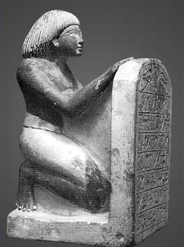 A painted limestone statuette of Roay, and 18th Dynasty scribe and royal steward, holding a rounded topped stela (a New Kingdom stelophorous)