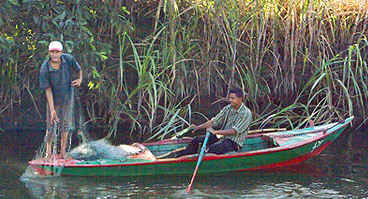 A small boat with fisherman on the Delta Canals.