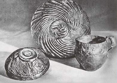 Two of the flimsy silver bows and a handled cup from the Tod Treasure, showing what many scholars believe to be Minoan influence