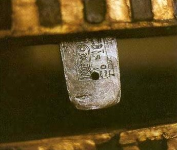An inscribed silver tenon, one of ten, attaching the lid and base of the second coffin