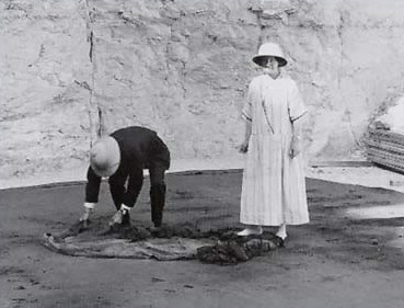 Professor Newberry and  his wife unroll the linen pall (no. 206) from the shrine of King Tut.